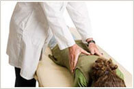 Chiropractor massages a woman who suffers from back pain
