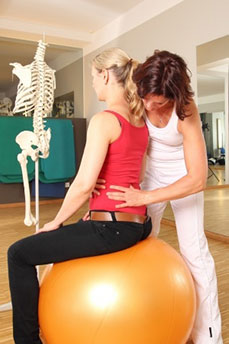 Chiropractor fixing a lady's back on a fit ball