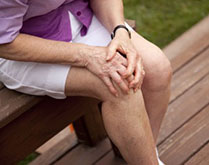 Man touches his knee because he suffers from osteoarthritis