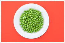 A big white plate full of peas